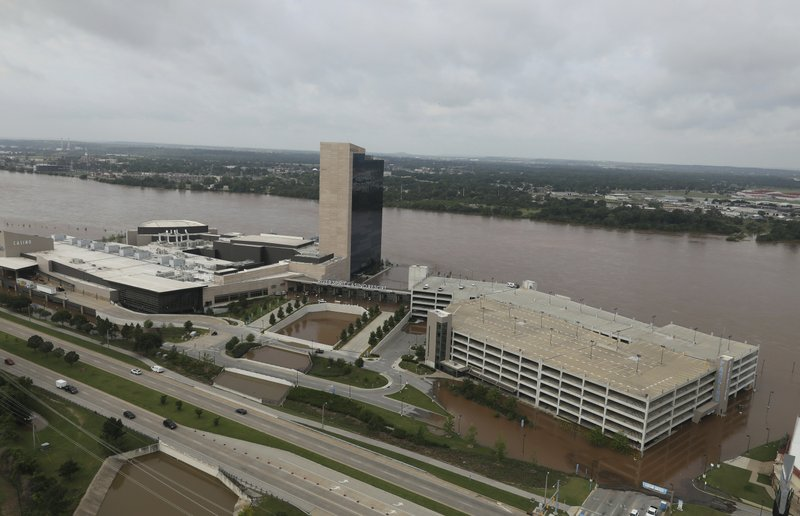 Flood waters cover the parking area of River Spirit Hotel and Casino on the Arkansas River on Friday, May 24, 2019, in Tulsa, Okla. (Tom Gilbert/Tulsa World via AP)