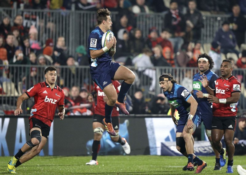 Blues Harry Plummer leaps in the air to take a catch during their Super Rugby match against the Crusaders in Christchurch, New Zealand, Saturday, May 25, 2019. (AP Photo/Mark Baker)