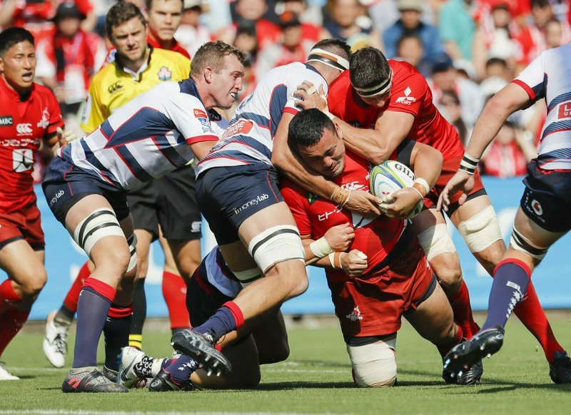 Sunwolves's Masataka Mikami, center, is tackled by Rebels defense during a Super Rugby match in Tokyo, Saturday, May 25, 2019. (Kyodo News via AP)