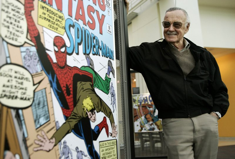 FILE - In this March 21, 2006 file photo, comic book creator Stan Lee stands beside some of his drawings in the Marvel Super Heroes Science Exhibition at the California Science Center in Los Angeles. A former business manager of Stan Lee has been arrested on elder abuse charges involving the late comic book icon. Los Angeles police say Keya Morgan was taken into custody in Arizona early Saturday, May 25, 2019, on an outstanding arrest warrant. Morgan was charged earlier this month with felony allegations of theft, embezzlement, forgery or fraud against an elder adult, and false imprisonment of an elder adult. (AP Photo/Damian Dovarganes, File)