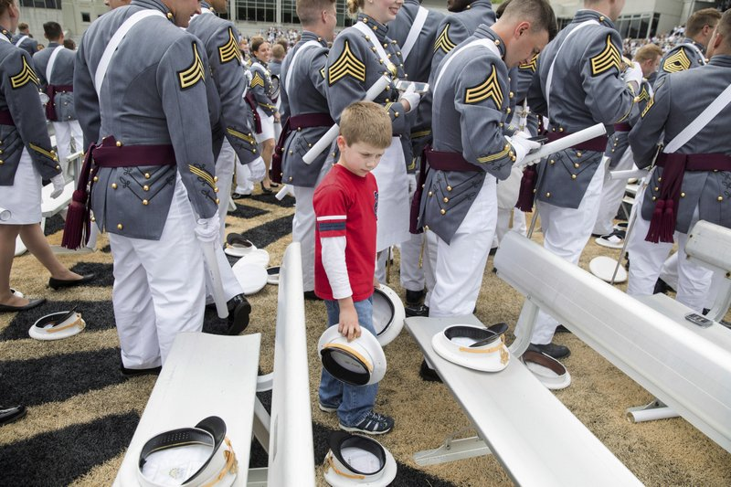 A child looks at cadets' caps at the end of graduation ceremonies at the United States Military Academy, Saturday, May 25, 2019, in West Point, N.Y. (AP Photo/Julius Constantine Motal)