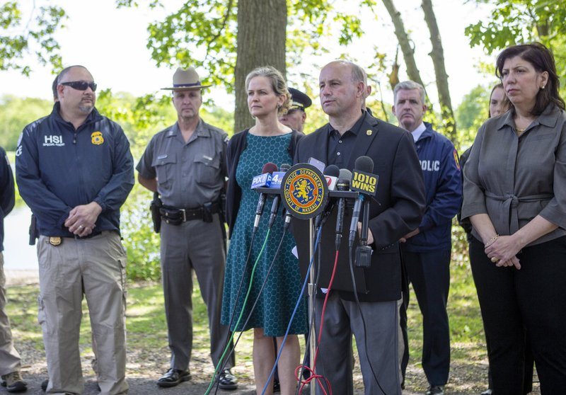 Nassau Police Commissioner Patrick Ryder, foreground right, speaks to the media on Saturday, May 25, 2019 in Massapequa, N.Y., after a body was found the day before at the Massapequa Preserve. Authorities believe the unidentified body is of a gang victim who was buried in the shallow grave more than two years ago. At right is Nassau County District Attorney Madeline Singas. Nassau County Executive Laura Curran is third from left. (Howard Schnapp/Newsday via AP)/