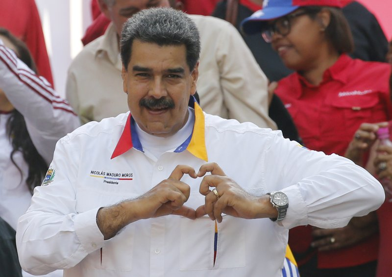 In this May 20, 2109 photo, Venezuela's President Nicolas Maduro flashes a hand-heart symbol to supporters outside Miraflores presidential palace in Caracas, Venezuela. Maduro said Thursday, May 23, 2019, that he iss inviting China's Huawei to help set up a 4G network in Venezuela, prompting opposition leader Juan Guaidó to accuse him of having an