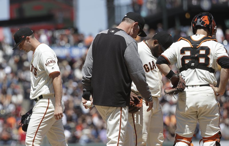 San Francisco Giants pitcher Andrew Suarez, left, walks off the mound after being relieved by manager Bruce Bochy, center, as third baseman Pablo Sandoval and catcher Buster Posey (28) wait during the fifth inning of a baseball game against the Arizona Diamondbacks in San Francisco, Saturday, May 25, 2019. (AP Photo/Jeff Chiu)
