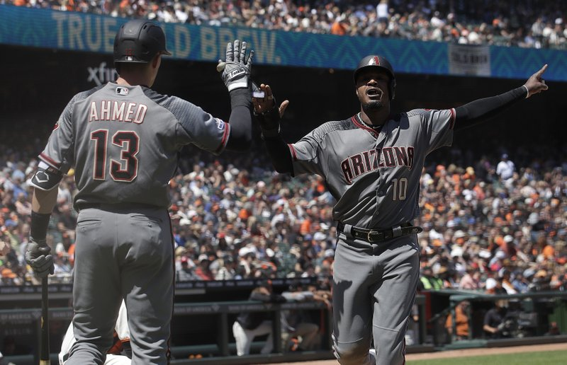 Arizona Diamondbacks' Adam Jones, right, is congratulated by Nick Ahmed after scoring a run against the San Francisco Giants during the fifth inning of a baseball game in San Francisco, Saturday, May 25, 2019. (AP Photo/Jeff Chiu)
