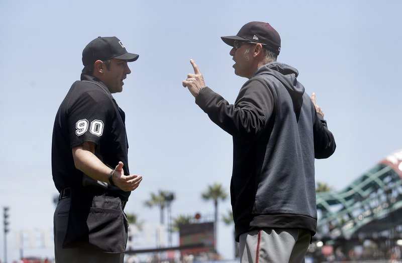 Arizona Diamondbacks manager Torey Lovullo, right, gestures while talking with umpire Mark Ripperger (90) before challenging a play during the first inning of a baseball game against the San Francisco Giants in San Francisco, Saturday, May 25, 2019. (AP Photo/Jeff Chiu)