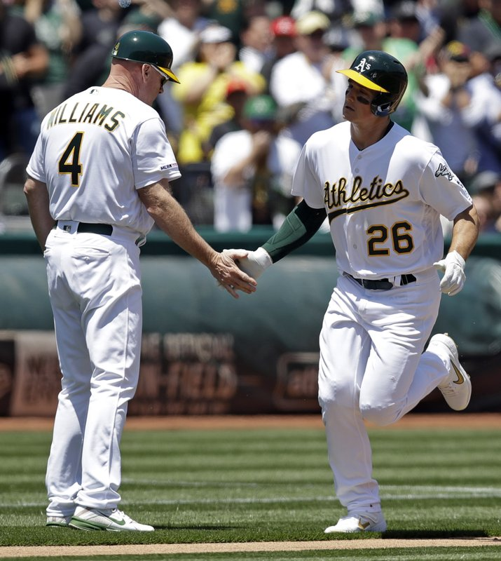 Oakland Athletics' Matt Chapman, right, is congratulated by third base coach Matt Williams, left, after hitting a home run off Seattle Mariners pitcher Yusei Kikuchi in the first inning of a baseball game Saturday, May 25, 2019, in Oakland, Calif. (AP Photo/Ben Margot)