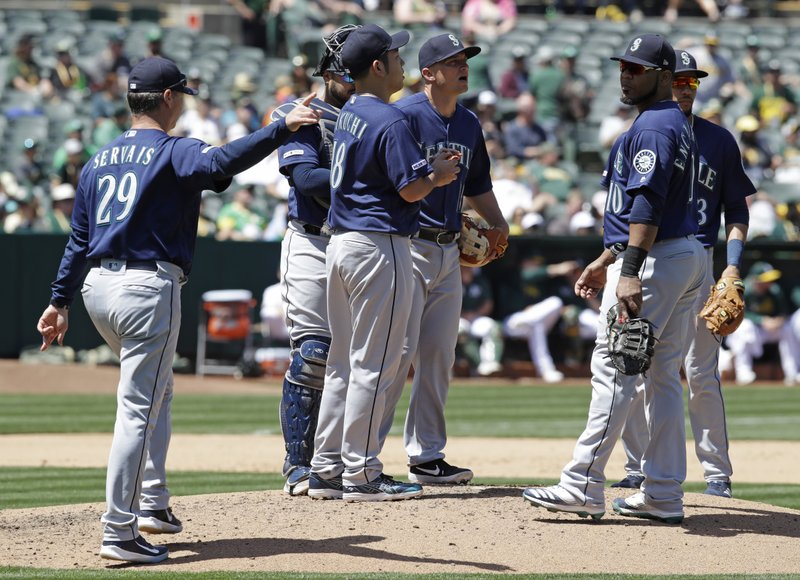 Seattle Mariners' Scott Servais, left, calls for a new pitcher as Yusei Kikuchi, center, is removed in the fourth inning of a baseball game against the Oakland Athletics, Saturday, May 25, 2019, in Oakland, Calif. (AP Photo/Ben Margot)