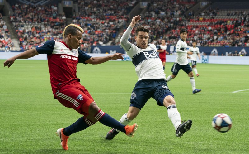FC Dallas' Michael Barrios, left, puts a shot on net past the defense of Vancouver Whitecaps' Victor Giro during the first half of an MLS soccer match Saturday, May 25, 2019, in Vancouver, British Columbia. (Richard Lam/The Canadian Press via AP)