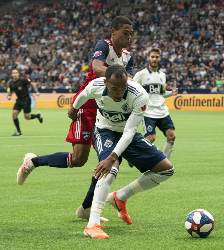 Vancouver Whitecaps' Derek Cornelius, front, tries to shield FC Dallas' Reggie Cannon from the ball during the first half of an MLS soccer match Saturday, May 25, 2019, in Vancouver, British Columbia. (Richard Lam/The Canadian Press via AP)