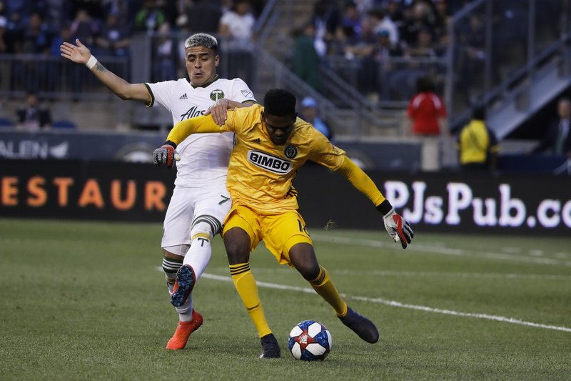 Portland Timbers' Brian Fernandez, left, and Philadelphia Union goalkeeper Andre Blake battle for the ball during the first half of an MLS soccer match in Chester, Pa., Saturday, May 25, 2019. (AP Photo/Matt Rourke)