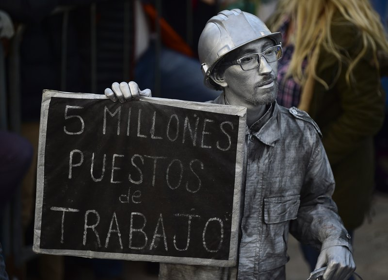 A man doused in silver body paint holds a sign with a message that reads in Spanish: