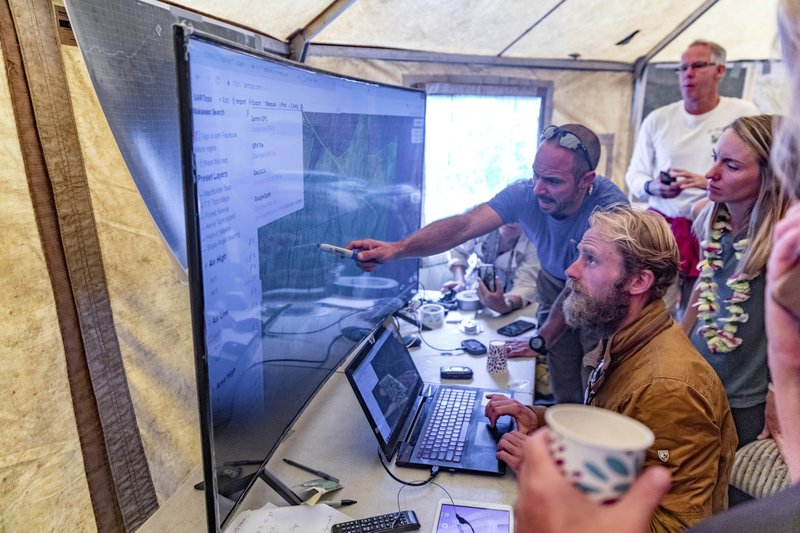 Rescue leads Javier Cantellops, top, and Chris Berquist show some of the technology used for the search of Amana Eller at the Makawao Forest Reserve base camp on Saturday, May 25, 2019 in Wailuku, Maui. The Maui News reported Friday Amanda Eller was found injured in the Makawao Forest Reserve. Family spokeswoman Sarah Haynes confirmed she spoke with Eller's father John. Eller was airlifted to safety. (Bryan Berkowitz/Honolulu Star-Advertiser via AP)