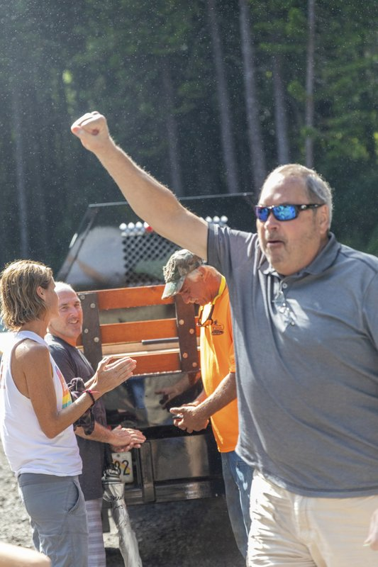 John Eller, right, father of Amanda Eller, reacts while acknowledging the crowd at the Makawao Forest Reserve base camp on Saturday, May 25, 2019 in Wailuku, Maui.. The Maui News reported Friday Amanda Eller was found injured in the Makawao Forest Reserve. Family spokeswoman Sarah Haynes confirmed she spoke with Eller's father John. Eller was airlifted to safety. (Bryan Berkowitz/Honolulu Star-Advertiser via AP)