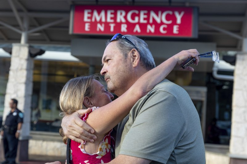 Sarah Haynes, left, embraces John Eller, father of Amanda Eller, outside the Maui Memorial Hospital on Friday, May 24, 2019 in Wailuku, Maui. The Maui News reported Friday Amanda Eller was found injured in the Makawao Forest Reserve. Family spokeswoman Sarah Haynes confirmed she spoke with Eller's father John. Eller was airlifted to safety. (Bryan Berkowitz/Honolulu Star-Advertiser via AP)