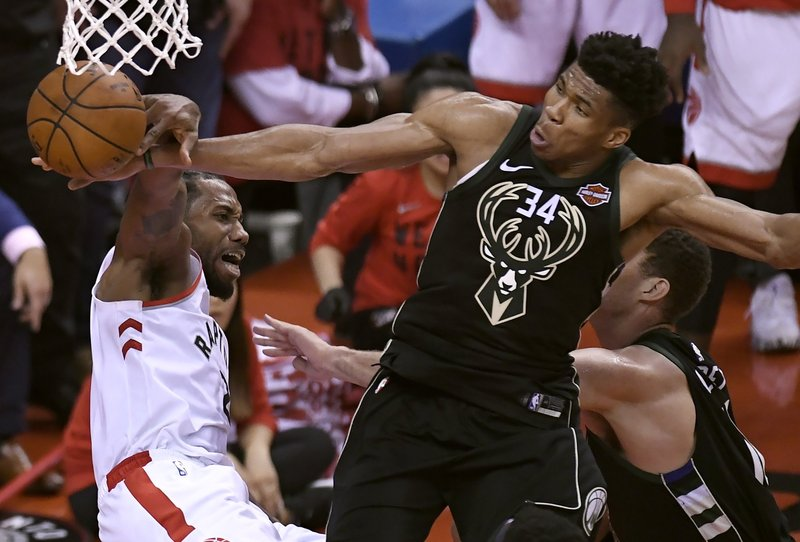 Milwaukee Bucks forward Giannis Antetokounmpo (34) blocks a dunk attempt by Toronto Raptors forward Kawhi Leonard, left, during the second half of Game 6 of the NBA basketball playoffs Eastern Conference finals Saturday, May 25, 2019, in Toronto. (Frank Gunn/The Canadian Press via AP)