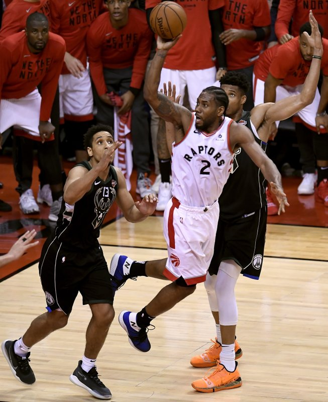 Toronto Raptors forward Kawhi Leonard (2) turns back to shoot the ball as Milwaukee Bucks' Malcolm Brogdon, left, and Giannis Antetokounmpo (34) defend during the second half of Game 6 of the NBA basketball playoffs Eastern Conference finals Saturday, May 25, 2019, in Toronto. (Frank Gunn/The Canadian Press via AP)