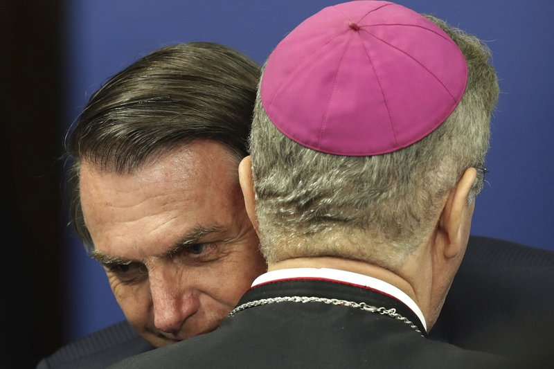 Brazil's President Jair Bolsonaro embraces Bishop Fernando Areas Rifan during a Catholic ceremony at which he dedicated his country to the Immaculate Heart of Mary at Planalto presidential palace in Brasilia, Brazil, Tuesday, May 21, 2019. During the ceremony, Bolsonaro was gifted an image of Our Lady of Fatima. (AP Photo/Eraldo Peres)