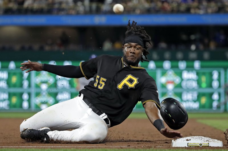 Pittsburgh Pirates' Josh Bell slides into third as a throw from Los Angeles Dodgers catcher Russell Martin gets past third baseman Max Muncy, allowing Bell to score, during the second inning of a baseball game in Pittsburgh, Saturday, May 25, 2019.  (AP Photo/Gene J. Puskar)