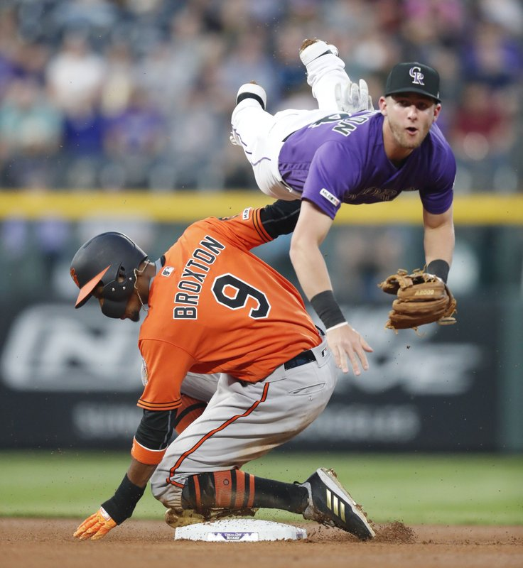 Colorado Rockies second baseman Ryan McMahon, top, flies over Baltimore Orioles' Keon Broxton after forcing  Broxton out at second on a ground ball hit by Stevie Wilkerson in the fourth inning of a baseball game Saturday, May 25, 2019, in Denver. (AP Photo/David Zalubowski)