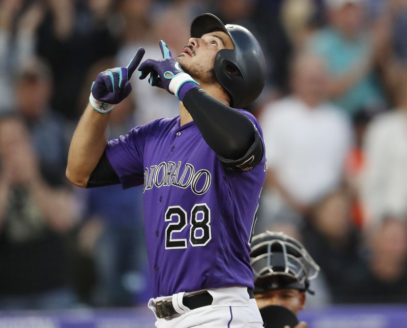 Colorado Rockies' Nolan Arenado gestures as he crosses home plate after hitting a three-run home run off Baltimore Orioles starting pitcher Andrew Cashner in the third inning of a baseball game Saturday, May 25, 2019, in Denver. (AP Photo/David Zalubowski)