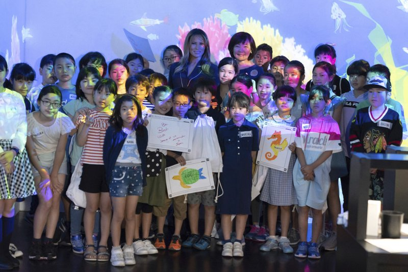 U.S. first lady Melania Trump poses with Akie Abe, center right, wife of Japanese Prime Minister Shinzo Abe, and children for a photo during a visit to a digital art museum in Tokyo Sunday, May 26, 2019. (Pierre-Emmanuel Deletree/Pool Photo via AP)