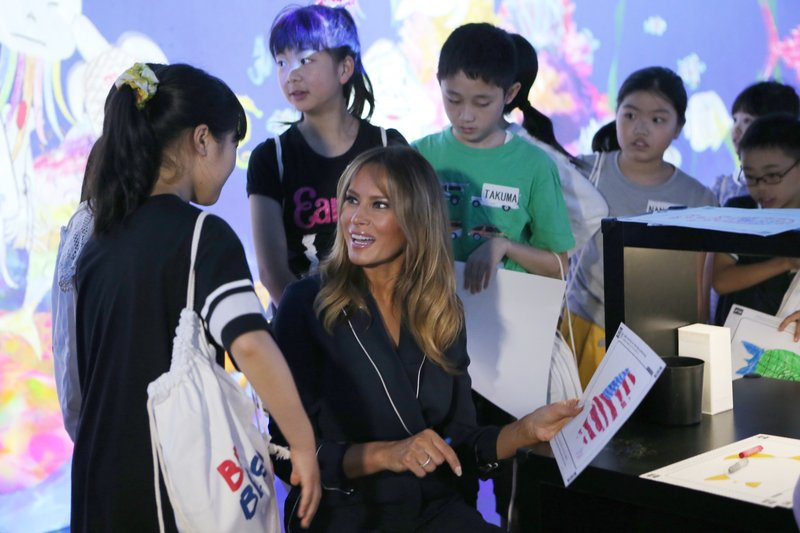 U.S. first lady Melania Trump chats with children as she visits a digital art museum Sunday, May 26, 2019, in Tokyo. (AP Photo/Koji Sasahara)