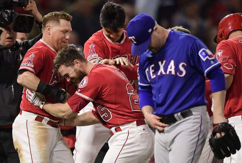 Los Angeles Angels' Jared Walsh, second from left, celebrates with Kole Calhoun, left, and Shohei Ohtani, center, of Japan, after Walsh hit a walk-off single. as Texas Rangers relief pitcher Shawn Kelley walks off the field at the end of the baseball game Saturday, May 25, 2019, in Anaheim, Calif. The Angels won 3-2. (AP Photo/Mark J. Terrill)