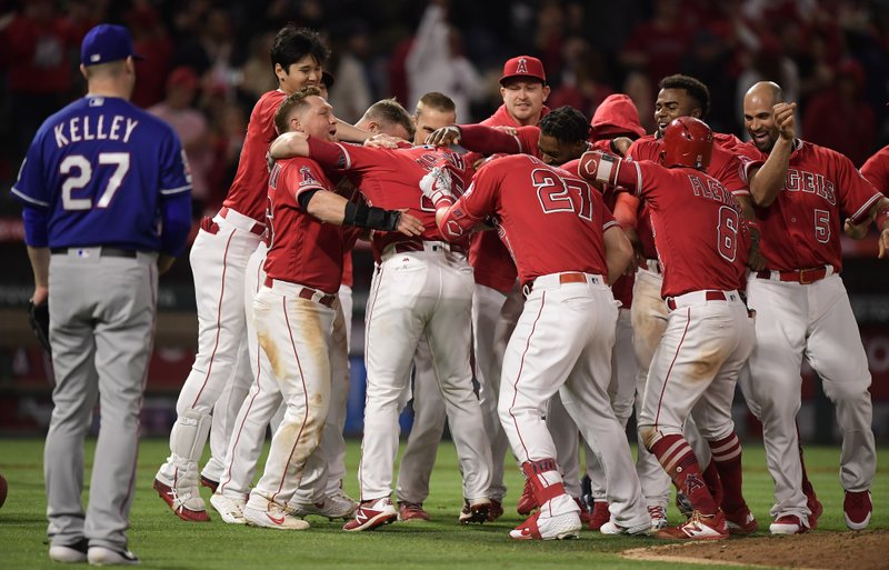 Los Angeles Angels celebrate after Jared Walsh, fourth from left, hit a walk-off single to score Kole Calhoun, to his left, as Texas Rangers relief pitcher Shawn Kelley watches at the end of a baseball game Saturday, May 25, 2019, in Anaheim, Calif. The Angels won 3-2. (AP Photo/Mark J. Terrill)