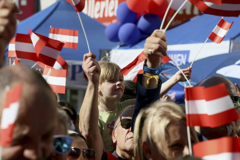 Supporters wave Austrian flags during the final election campaign event of the right-wing Freedom Party, FPOE, for European elections in Vienna, Austria, Friday, May 24, 2019. (AP Photo/Ronald Zak)