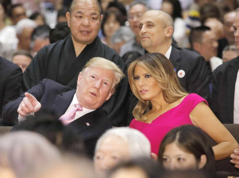 U.S. President Donald Trump, left, and first lady Melania Trump, right, chat during an annual summer sumo wrestling championship in Tokyo, Sunday, May 26, 2019. (Daiki Katagiri/Kyodo News via AP)