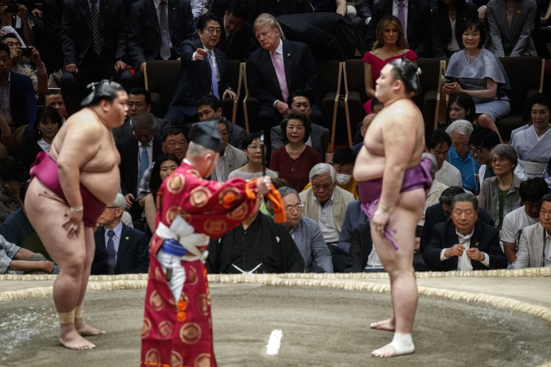 President Donald Trump attends the Tokyo Grand Sumo Tournament with Japanese Prime Minister Shinzo Abe at Ryogoku Kokugikan Stadium, Sunday, May 26, 2019, in Tokyo. At top right is Akie Abe and second from right is first lady Melania Trump. (AP Photo/Evan Vucci)