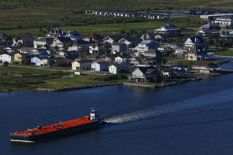 In this Wednesday, Sept. 7, 2016 photo, a barge passes by homes on the Bolivar Peninsula in Galveston, Texas. A dike, called the