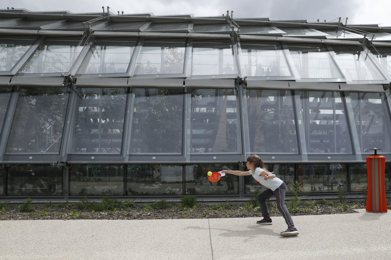 A girl catches a tennis ball with her cap outside the new Simonne Mathieu court at the Jardin des Serres d'Auteuil botanical garden during their first round match of the French Open tennis tournament at the Roland Garros stadium in Paris, Sunday, May 26, 2019. (AP Photo/Pavel Golovkin)