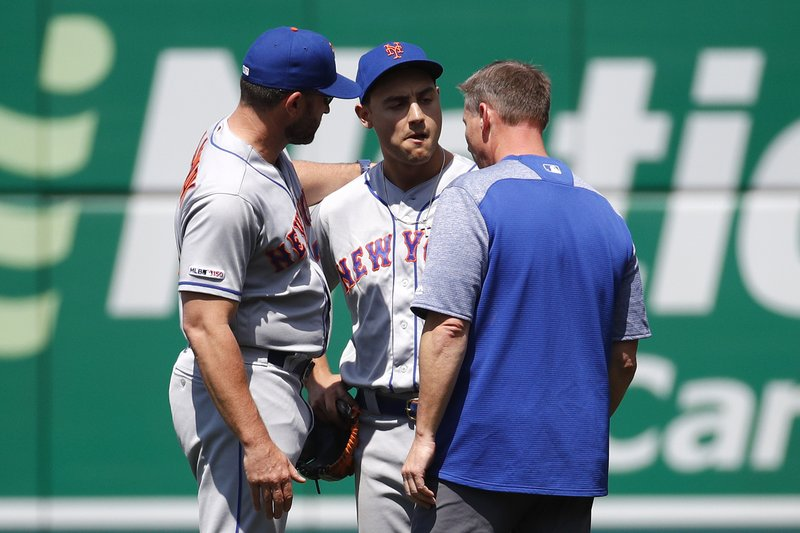 New York Mets right fielder Michael Conforto, center, speaks with manager Mickey Callaway, left, and a member of the Mets staff after colliding with second baseman Robinson Cano as they failed to catch a fly ball that was hit by Washington Nationals' Howie Kendrick in the fifth inning of a baseball game, Thursday, May 16, 2019, in Washington. Conforto left the game after the play. (AP Photo/Patrick Semansky)