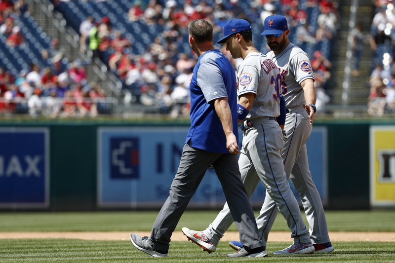 New York Mets right fielder Michael Conforto, center, walks off the field with manager Mickey Callaway, right, and a member of the Mets staff after colliding with second baseman Robinson Cano as they failed to catch a fly ball that was hit by Washington Nationals' Howie Kendrick in the fifth inning of a baseball game, Thursday, May 16, 2019, in Washington. (AP Photo/Patrick Semansky)