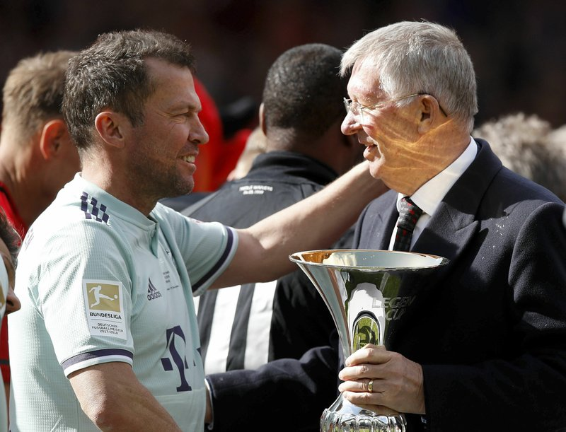 Manchester United Legends manager Sir Alex Ferguson with the trophy is congratulated by Bayern Munich Legends Lothar Matthaus after the legends match between Manchester United Legends and Bayern Munich Legens at Old Trafford, Manchester, England, Sunday, May 26, 2019. (Martin Rickett/PA via AP)
