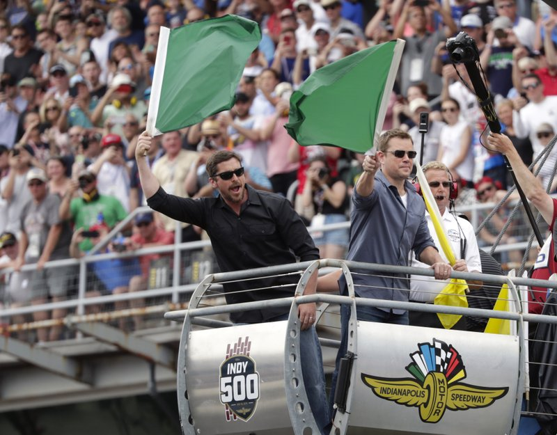 Actors Matt Damon, right, and Christian Bale wave green flags to start Indianapolis 500 IndyCar auto race at Indianapolis Motor Speedway, Sunday, May 26, 2019, in Indianapolis. (AP Photo/Michael Conroy)