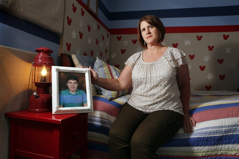 Julie Callahan of Grove City with a portrait of her son Jackson in his bedroom at her home May 23, 2019.A supportive mother, but Franklin County Children Services has custody of her 14-year-old son. Callahan is one of many Ohio parents who surrender custody in order to obtain desperately needed , and very expensive, mental-health treatment for their kids. Despite years of promises, the state has failed on most all of its plans to fix the problem. Her son Jackson is now at a hospital in Cincinnati. (Eric Albrecht/The Columbus Dispatch via AP)