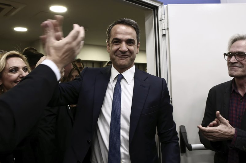 Greek opposition New Democracy party leader Kyriakos Mitsotakis shakes hands with a supporter after his statements in Athens on Sunday, May 26, 2019. Greek prime minister Tsipras calls for a snap national election following European election loss. (Panayiotis Tzamaros/InTime News via AP)