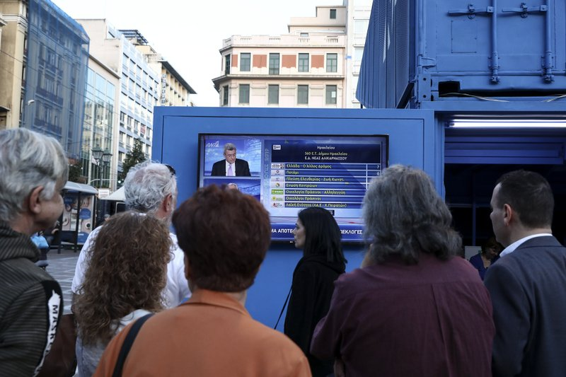People watch European election results at a campaign kiosk of New Democracy opposition party, in Athens, Sunday, May 26, 2019. New Democracy party is projected to win the European election, according to an exit poll jointly conducted by five Greek polling firms. (AP Photo/Yorgos Karahalis)