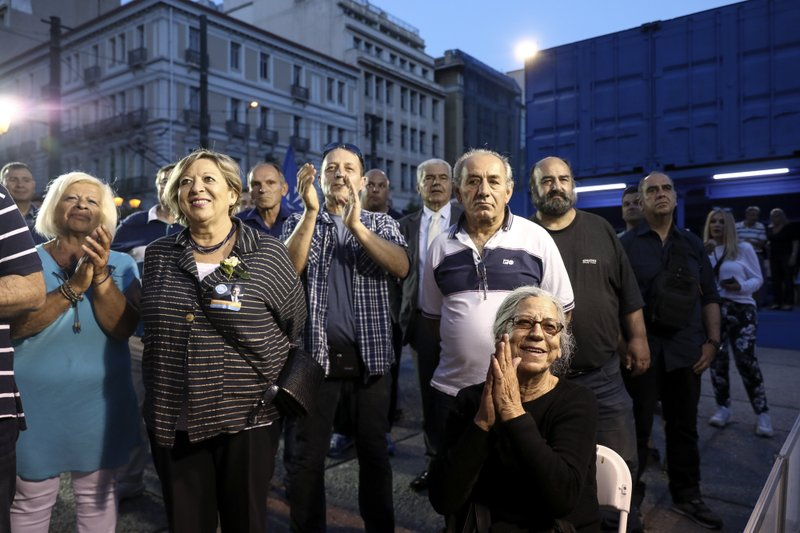 Supporters of New Democracy opposition conservative party react as they watch an exit poll at a campaign kiosk, in Athens, Sunday, May 26, 2019. New Democracy party is projected to win the European election, according to an exit poll jointly conducted by five Greek polling firms. (AP Photo/Yorgos Karahalis)
