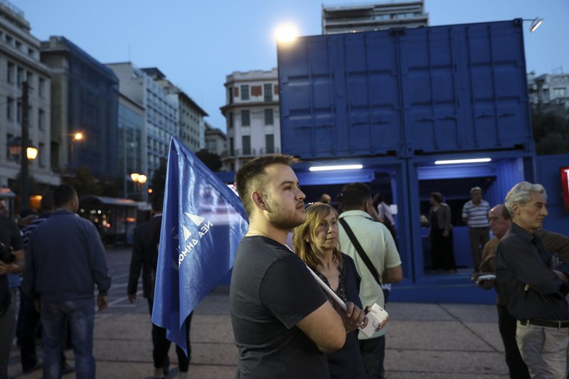 A supporter of New Democracy opposition party watches European elections results at a campaign kiosk, in Athens, Sunday, May 26, 2019. New Democracy party is projected to win the European election, according to an exit poll jointly conducted by five Greek polling firms. (AP Photo/Yorgos Karahalis)