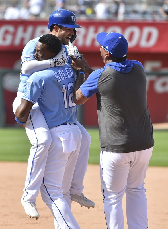 Kansas City Royals' Whit Merrifield, back left, is congratulated by Jorge Soler (12) and Salvador Perez after hitting a game-winning RBI single in the 10th inning against the New York Yankees during a baseball game Sunday, May 26, 2019, in Kansas City, Mo. The Royals won 8-7. (AP Photo/Ed Zurga)