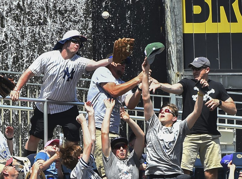 Fans try to catch a home run ball hit by Kansas City Royals' Hunter Dozier in the fifth inning during a baseball against the New York Yankees game Sunday, May 26, 2019, in Kansas City, Mo. (AP Photo/Ed Zurga)