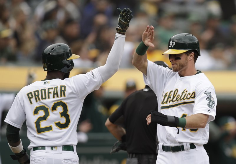 Oakland Athletics' Skye Bolt, right, celebrates with Jurickson Profar (23) after they scored against the Seattle Mariners in the seventh inning of a baseball game Sunday, May 26, 2019, in Oakland, Calif. They scored on a double by Josh Phegley. (AP Photo/Ben Margot)