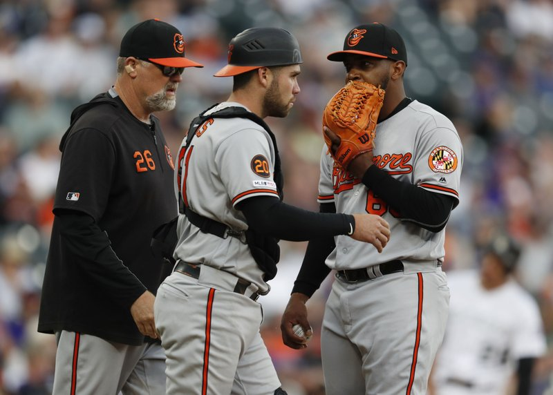 Baltimore Orioles relief pitcher Mychal Givens, right, confers with catcher Austin Wynns, center, as pitching coach Doug Brocail heads to the mound before Giens faces Colorado Rockies' Ian Desmond in the ninth inning of a baseball game Sunday, May 26, 2019, in Denver. (AP Photo/David Zalubowski)