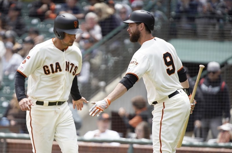 San Francisco Giants' Brandon Belt (9) congratulates Joe Panik, left, after Panik scored on a double by Buster Posey against the Arizona Diamondbacks during the first inning of a baseball game in San Francisco, Sunday, May 26, 2019. (AP Photo/Tony Avelar)