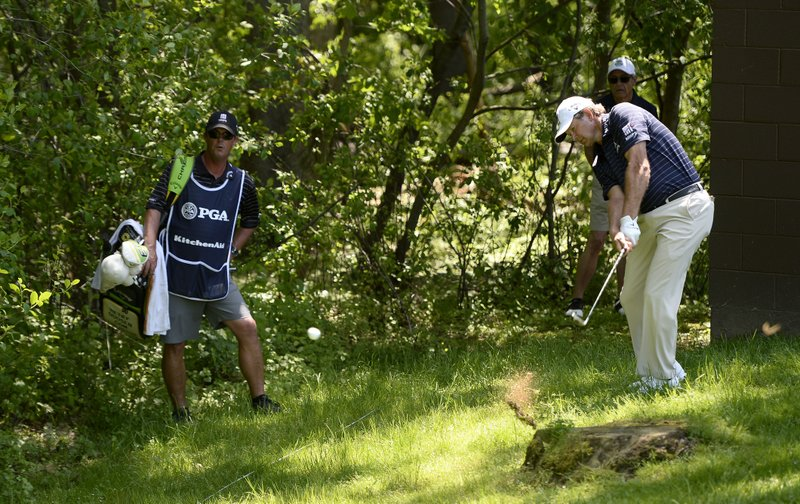 Retief Goosen, right, hits from the rough on the second hole during the final round of the Senior PGA Championship golf tournament, Sunday, May 26, 2019, in Rochester, N.Y. (AP Photo/Adrian Kraus)