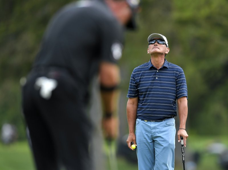 Ken Tanigawa, right, takes a moment while waiting for Scott McCarron to putt on the 17th green during the final round of the Senior PGA Championship golf tournament, Sunday, May 26, 2019, in Rochester, N.Y. Tanigawa won the championship. (AP Photo/Adrian Kraus)